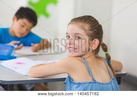 Portrait of happy schoolgirl in classroom at school
