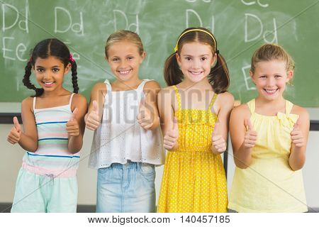 Portrait of smiling kids showing thumbs up in classroom at school