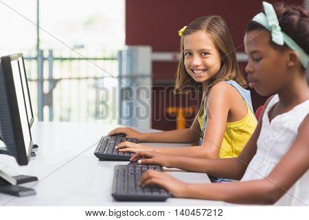 Portrait of Schoolgirls using computer in classroom at school