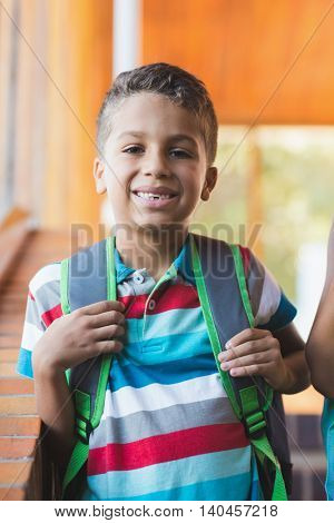 Portrait of smiling school boy standing in school corridor