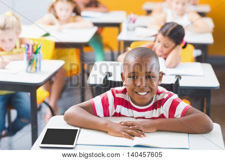 Disabled schoolboy smiling in classroom at school