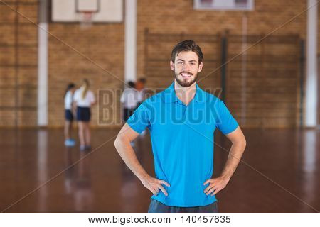 Portrait of sports teacher standing with hands on hip in basketball court at school gym