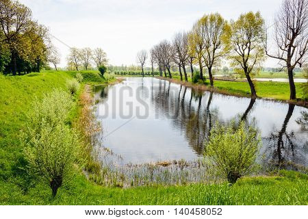Rampart and moat of the Dutch castle Loevestein in the spring season. The budding trees are reflected in the smooth water surface.