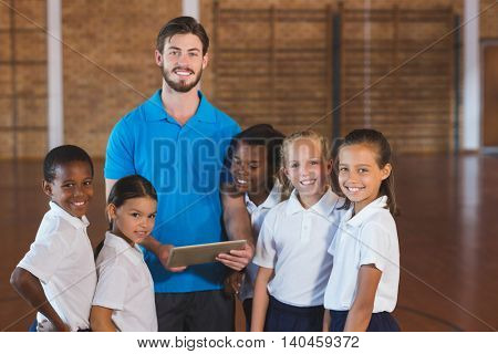 Portrait of sports teacher and school kids using digital tablet in basketball court at school gym