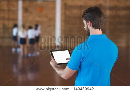 Sports teacher using digital tablet in basketball court at school gym