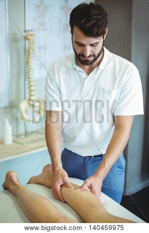Physiotherapist giving leg massage to a woman in clinic