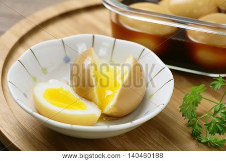 Runny eggs on white bowl with braised eggs on wooden table