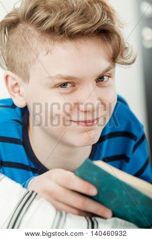 Teenage Boy Relaxing In Bed While Reading Book