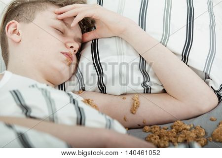 Teenage Boy Lying In Bed Covered In Vomit