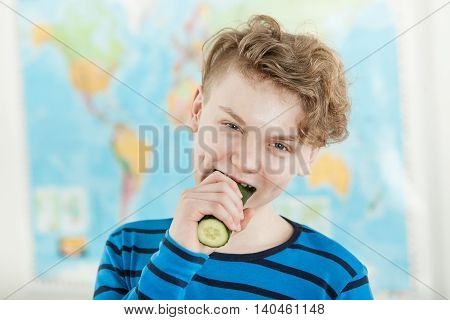 Teenage Boy Eating Whole Cucumber In Front Of Map