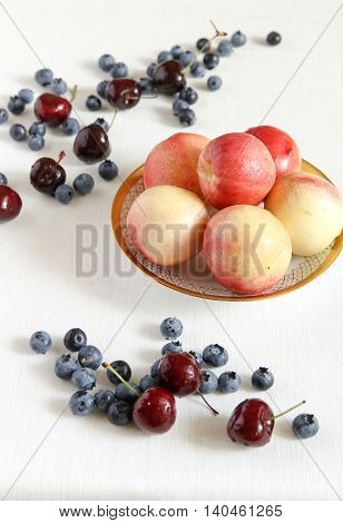 Berry mix. Peaches in a bowl cherry and bilberry. A white cloth from flax.