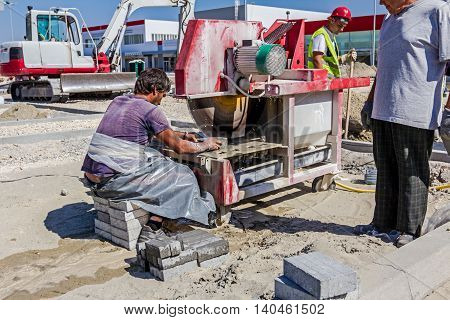 Zrenjanin Vojvodina Serbia - September 14 2015: Worker using abrasive action to slice through concrete brick as the blade rotates at high speed.