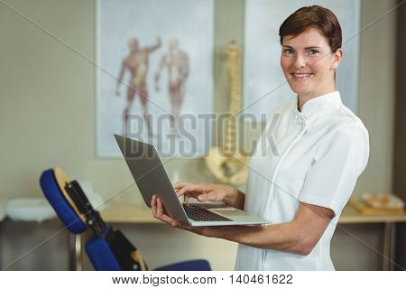 Portrait of physiotherapist using a laptop in the clinic