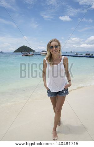 Smiling pretty blonde wearing jeans shorts, white t-shirt and sunglasses on the beach over sea and sky background