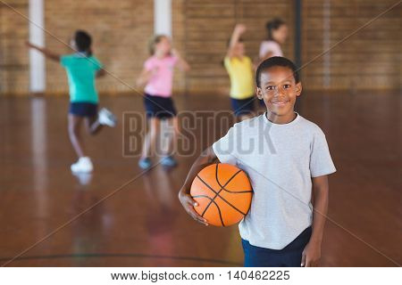 Boy standing with ball in basketball court at school gym