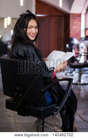 Portrait of woman reading a magazine while waiting with hair dye in her head at a salon