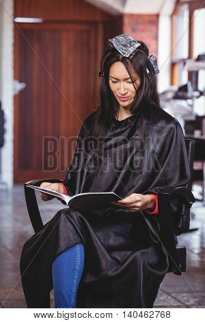 Woman reading a magazine while waiting with hair dye in her head at a salon