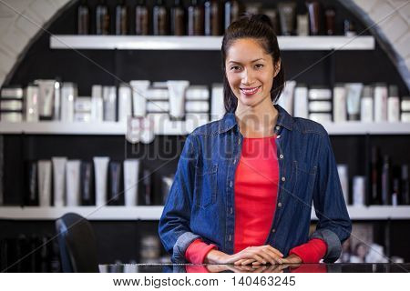 Portrait of female hairdresser standing at a table in salon