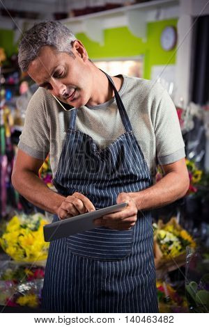 Male florist taking order on mobile phone while using digital tablet at his shop