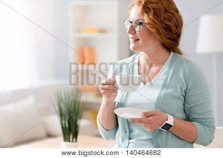In harmony with mind. Pleasant delighted beautiful senior woman leaning on the table and drinking tea while resting at home
