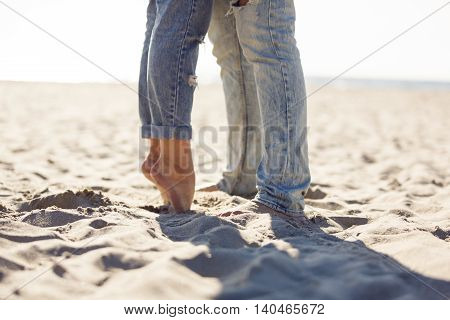 Legs of couple are standing on the beach summer time