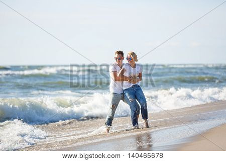 Cheerful couple are hugging on the beach summer time