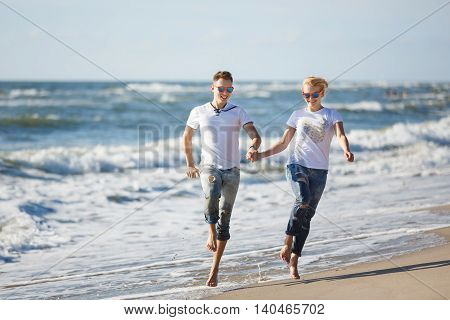 Cheerful couple are running along the seacoast at summer time
