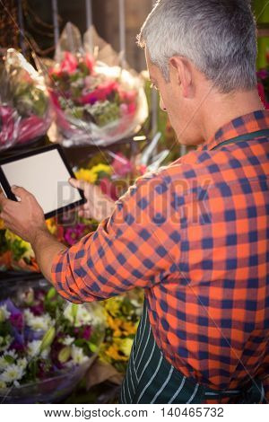 Male florist taking photo of flower bouquet on digital tablet at his flower shop