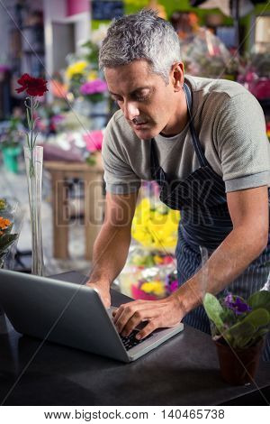 Close-up of male florist using laptop at his flower shop