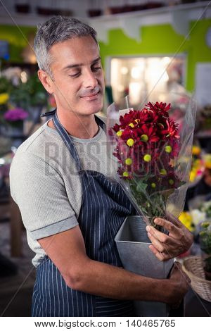Happy male florist holding bunch of red sunflower in vase at his flower shop