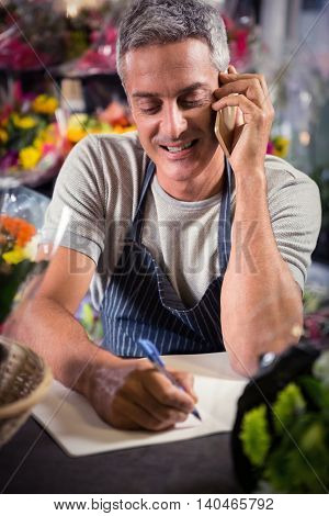Close-up of male florist taking order on mobile phone at his flower shop