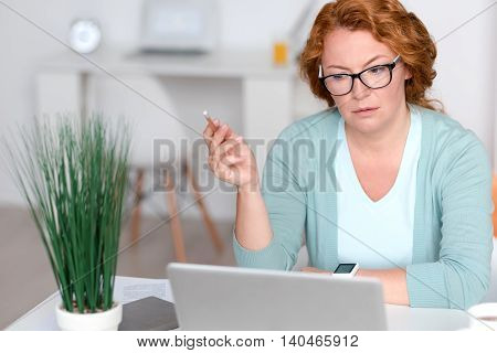Find solution. Pleasant baffled senor woman sitting at the table and using laptop while being involved in work