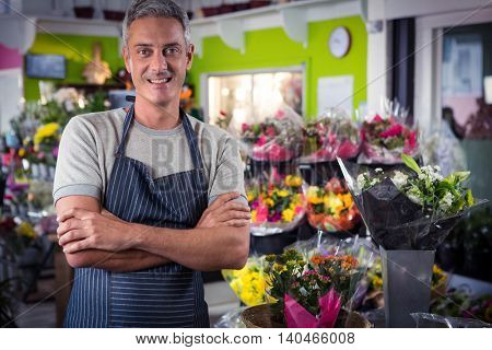 Portrait of happy male florist standing with arms crossed at his flower shop