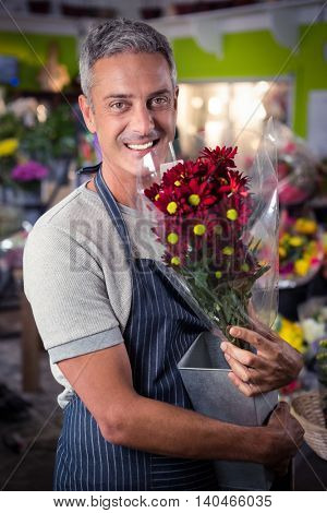Portrait of happy male florist holding bunch of red sunflower in vase at his flower shop
