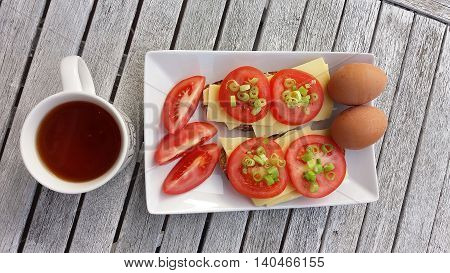 photo of breakfast: cup of tea eggs and sandwiches with cheese toamatoes and chives on white plate on wooden table