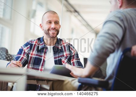 Front view of businessmen discussing with colleagues in creative office