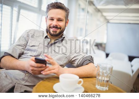 Portrait of smiling businessman using mobile phone while sitting in creative office