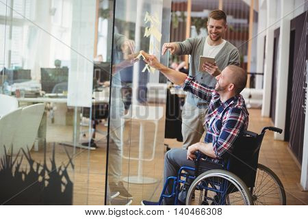 Businessman assisting handicap colleague while sticking adhesive notes on glass window in creative office