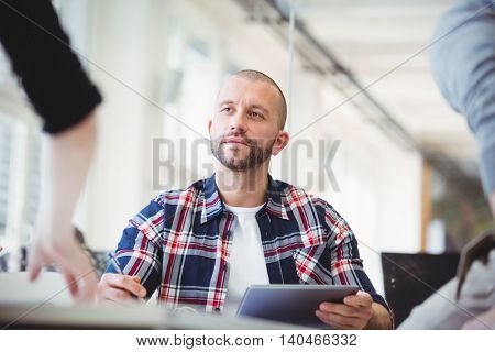 Front view of businessmen using digital tablet discussing with colleagues in creative office
