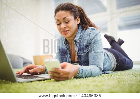 Businesswoman using mobile phone while using laptop in creative office