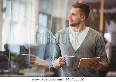 Happy businessman holding coffee cup with digital tablet in office