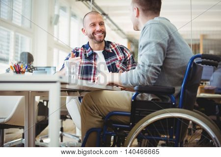 Handicap businessman discussing while sitting with colleague in creative office