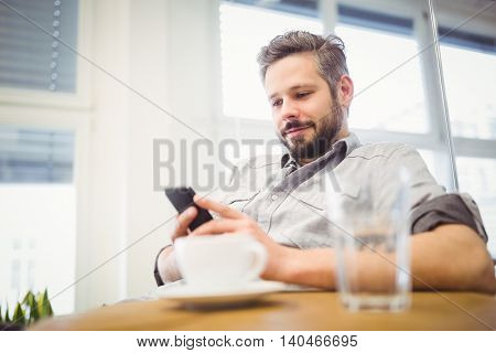 Smiling businessman using mobile phone while sitting in creative office
