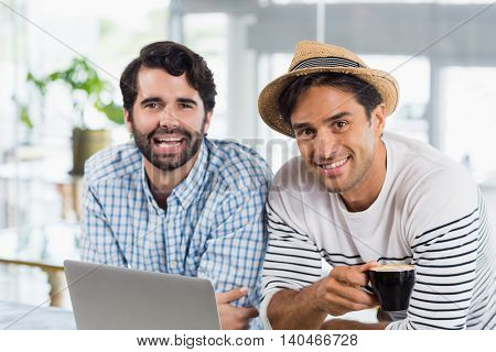 Portrait of two friends using laptop while having cup of coffee in cafe