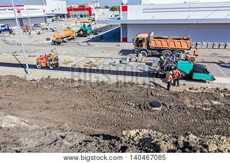 Zrenjanin Vojvodina Serbia - September 14 2015: Hot asphalt is applied to the ground by construction crew with tarmac road laying machine.