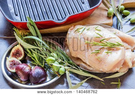 Cooking chicken breasts on the grill. On the table are spices - rosemary red and black pepper figs and olives on a branch. Concept - healthy food.