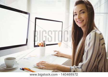Portrait of businesswoman working on computer in creative office