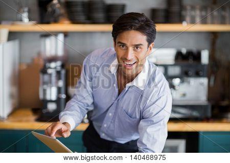 Portrait of smiling man using digital tablet in cafe