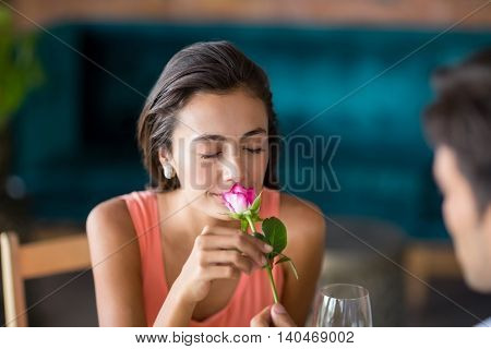 Woman smelling a rose offered by man in restaurant