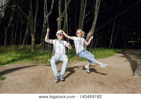 Cheerful couple on the swing in the forest summer time